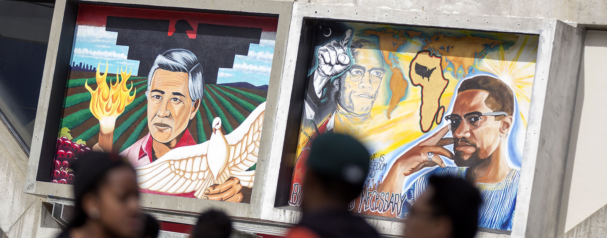 Students talking near murals of Cesar Chavez and Malcolm X