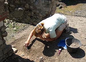 Una foto d'un estudiant en el sòl l'eliminació d'una excavació arqueològica com a part de San Francisco de l'Estat escola en el camp arqueològic de Pompeia.