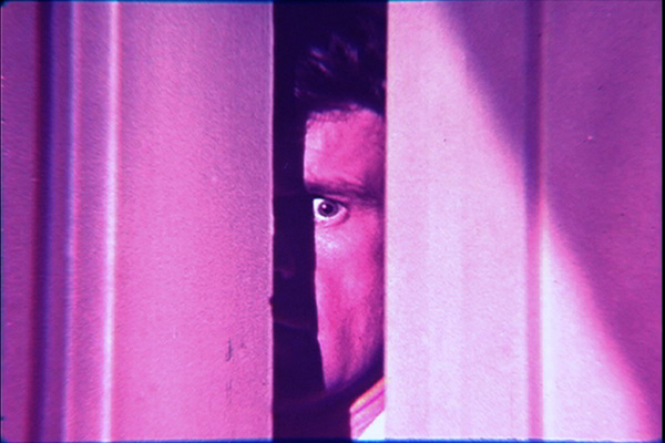 A shot from the film in which a man is peering into a room through a slightly opened door.