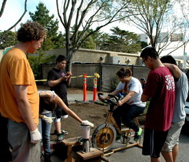 A photo of students making a smoothie using a blender powered by a stationary bicycle