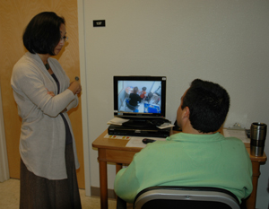A photo of Professor Yu with a parent who is watching his young son's progress from a remote computer screen.