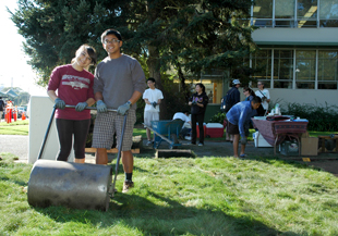 Photo of two students pushing a heavy rolling machine over the newly laid turf