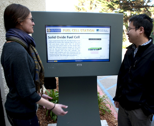 A photo of students from the Engineering Department demonstrating the educational touch-screen kiosk outside the fuel cell plant.