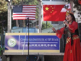 A photo of a Chinese singer in front of the American and Chinese flags and a Confucius Institute SFSU banner.