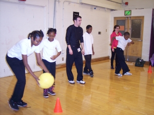 A photo of SF State students Justin Birdsell and Ashley Hooper working with students during Outreach Day at the Willie Brown Academy.