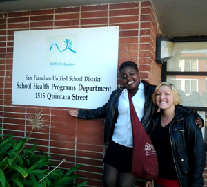 Students Kayla Daniels and Vaneka Reed in front of a sign for the San Francisco Unified School District's School Health Programs Department.