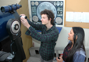 A photo of SF State students Simon Bacholle and Priyanjoli Mukherjee working with a telescope in the SF State observatory.