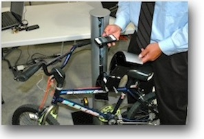 A photo of a student demonstrating a Bluetooth enabled bicycle lock.