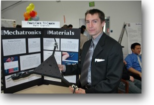 A photo of Mark Gianni holding a tricopter made of foam core board.