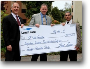 Photo of Bruce Berardi, senior vice president of Lend Lease, and Peter Read, vice president of Lend Lease, presenting a check to TAB Program Coordinator Paul Mendez.